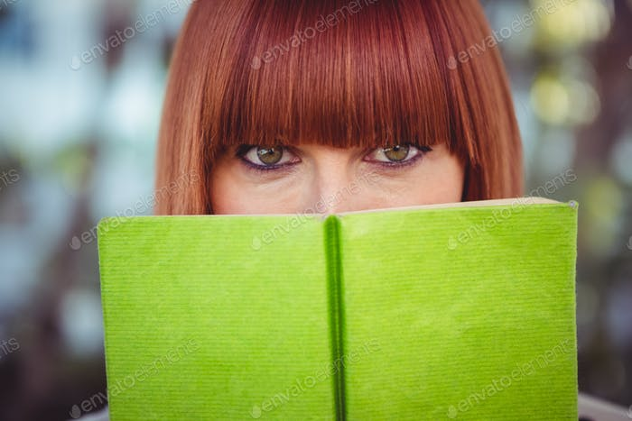 Attractive hipster woman reading a book in the garden