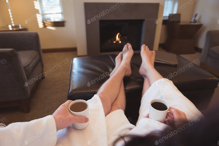 Couple relaxing while having coffee in the living room