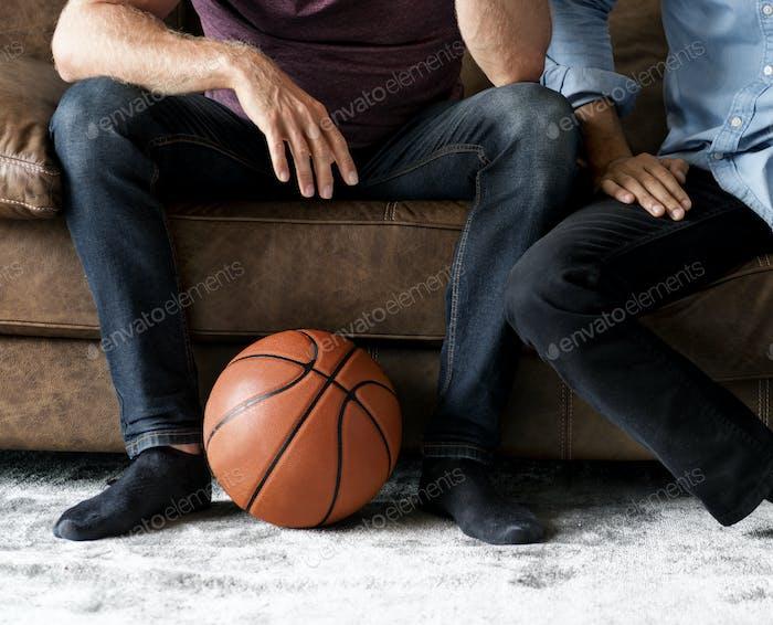 Mann sitzt zusammen auf einer Couch beobachten Sport