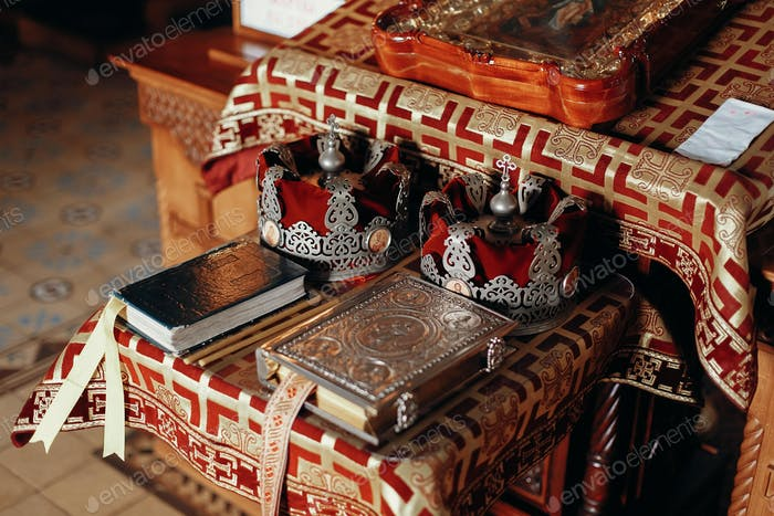 Golden bible, gospel,  crowns and cross and icon on red and gold altar in church