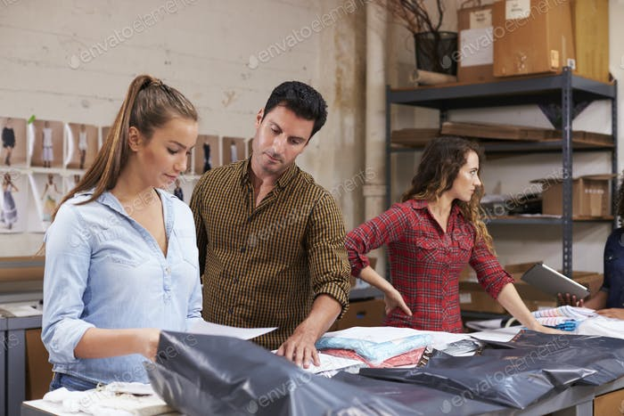 Male manager with trainee packing orders for distribution