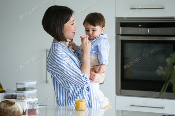 Beautiful mother feeding her baby porridge in the kitchen at home.