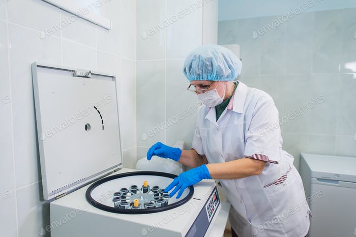 Closeup of a senior female chemist setting up some sample blood tubes inside a centrifuge for some