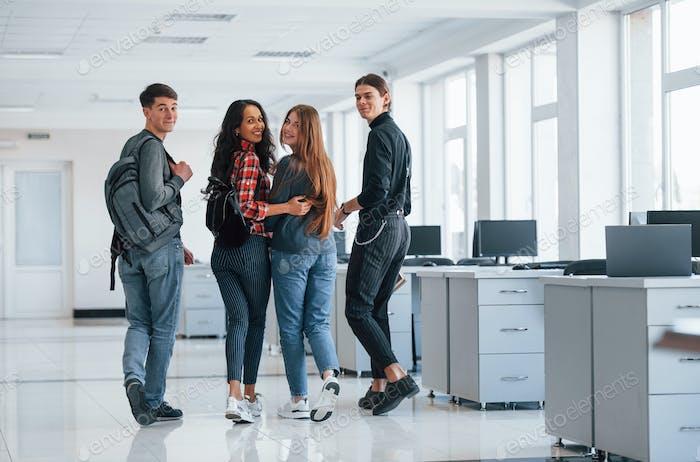 Freundschaft und Umarmungen. Gruppe junger Leute, die zu ihrer Pause ins Büro gehen