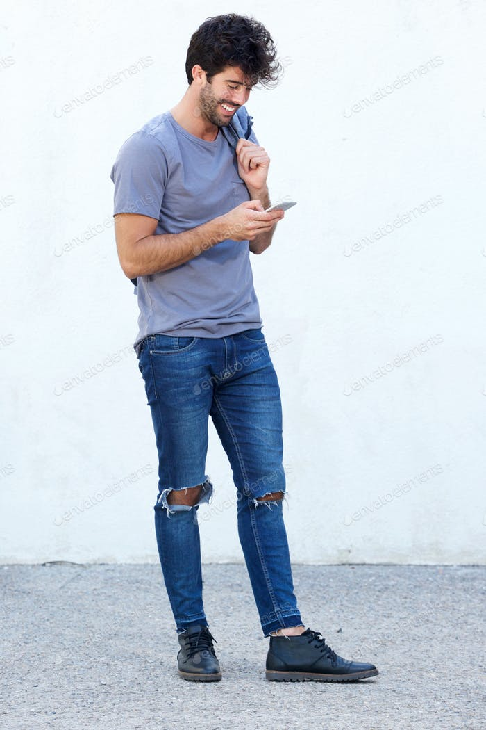 Full body handsome happy man holding mobile phone and jacket
