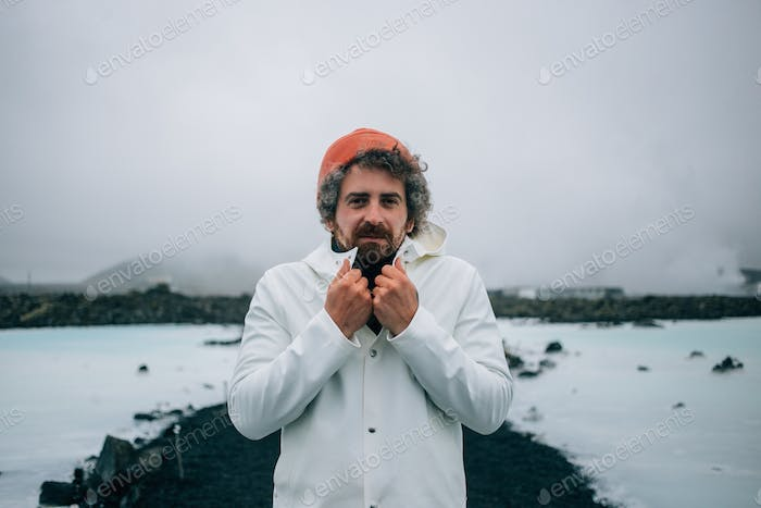 Cold man in white raincoat in iceland