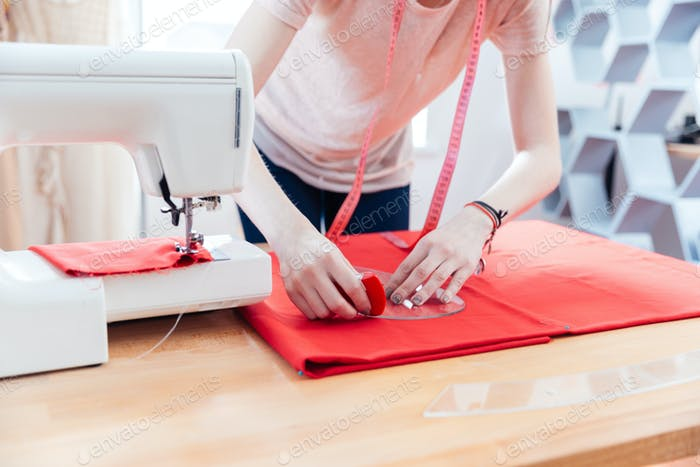 Woman seamstress working making pattern on red fabric
