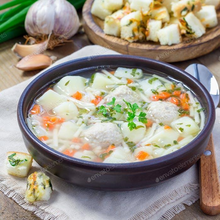 Hausgemachte Suppe mit Fleischbällchen und Gemüse, serviert mit Käse Knoblauch Petersilie Croutons, quadratisch