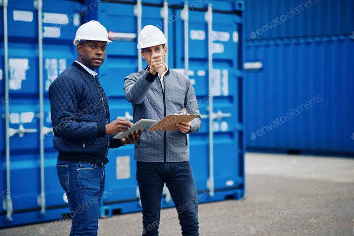 Two engineers discussing freight logistics on a shipping dock