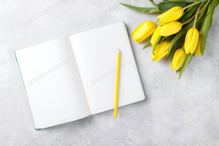 Blank notepad and yellow tulips