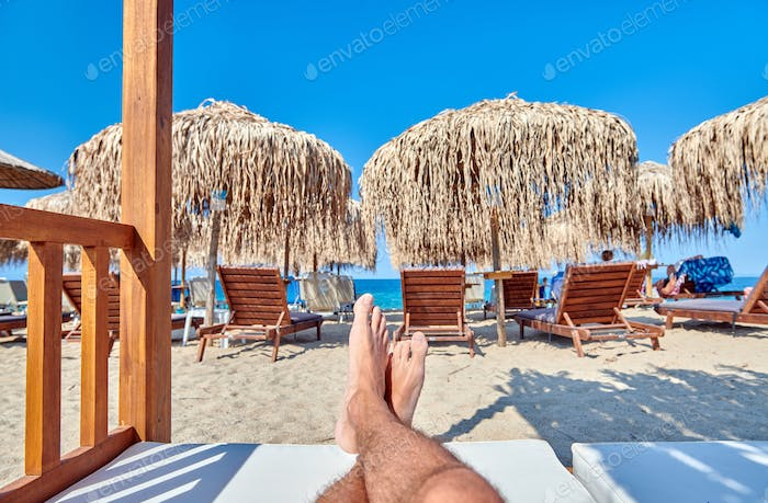 Man's legs in beach lounger