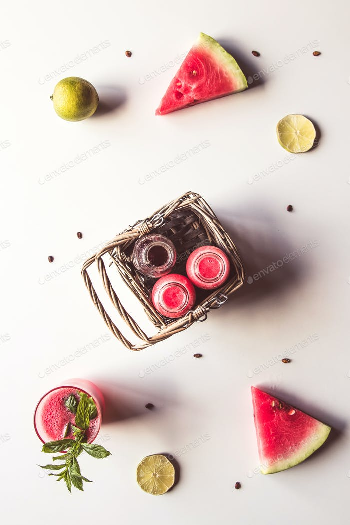 Tasty summer bottled watermelon drink in a basket and slices of fresh fruits on white background