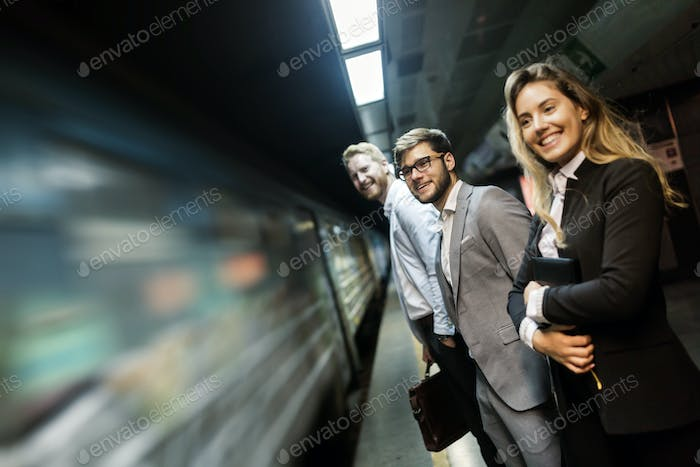 Business people waiting for subway and smiling