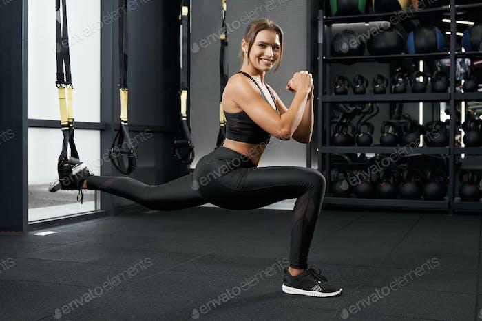 Lächelnde Frau beim Training mit dem TRX-Systemsystem