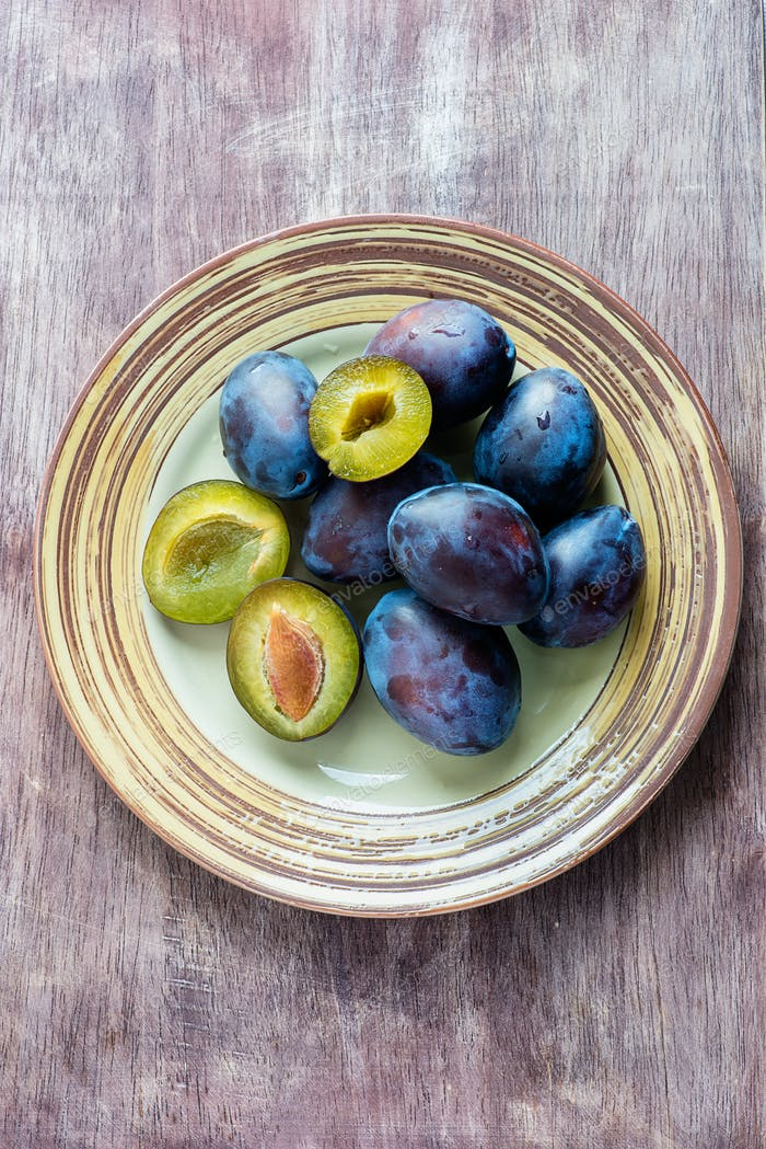 Fresh plums on plate  over wooden background