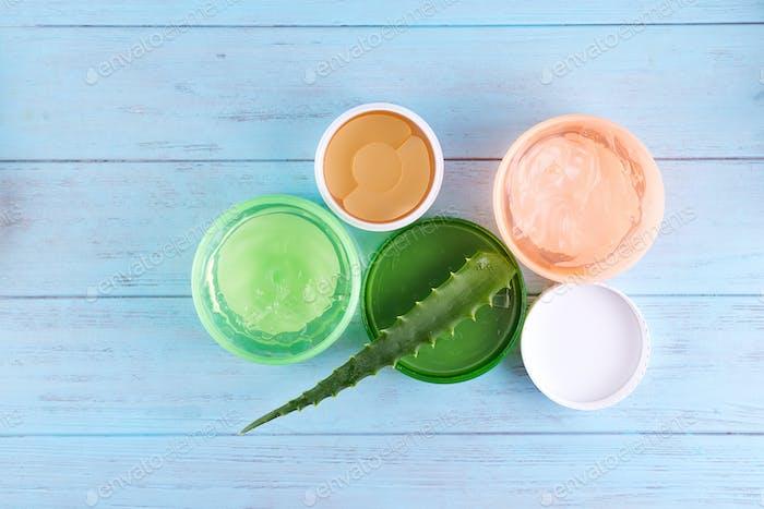 gel serum of snail collagen and Fresh Aloe Vera Gel in jar on blue wooden background. Snail gel is