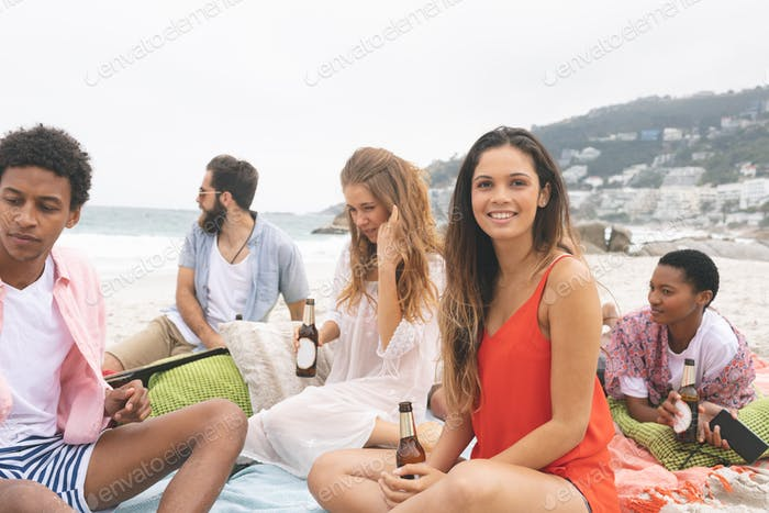Front view of multi ethnic woman relaxing with friends while looking at camera