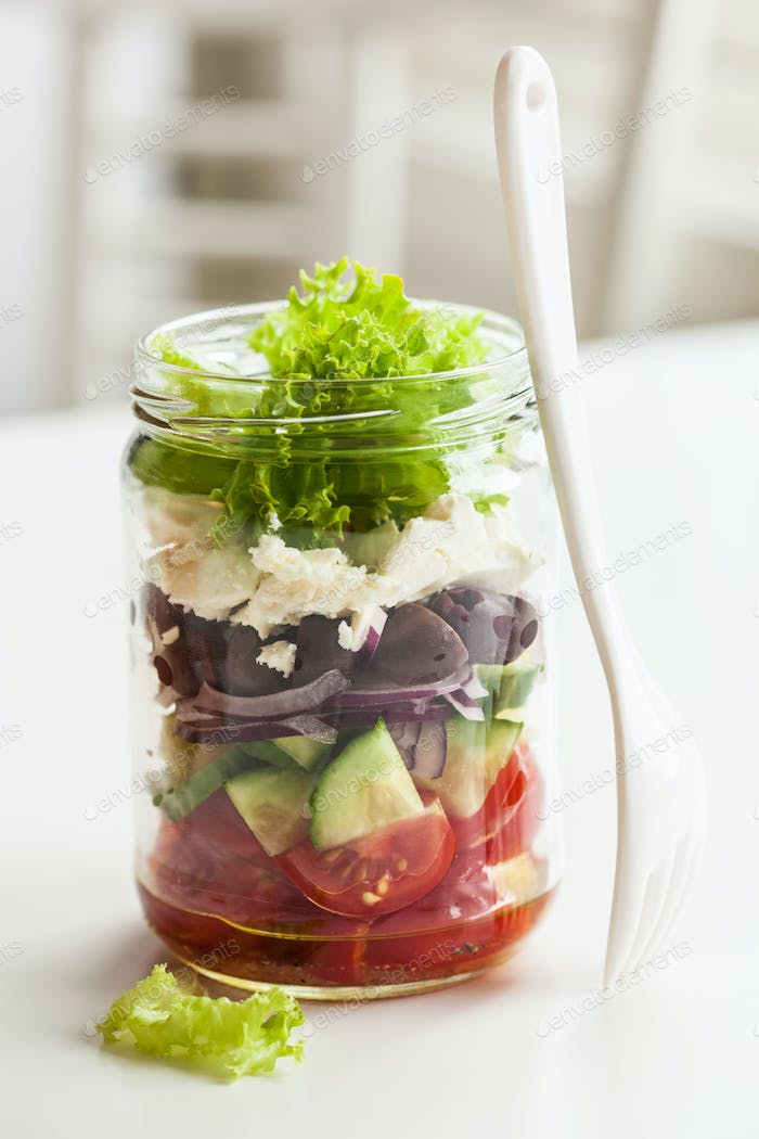 healthy greek salad in mason jar. tomato olive feta onion