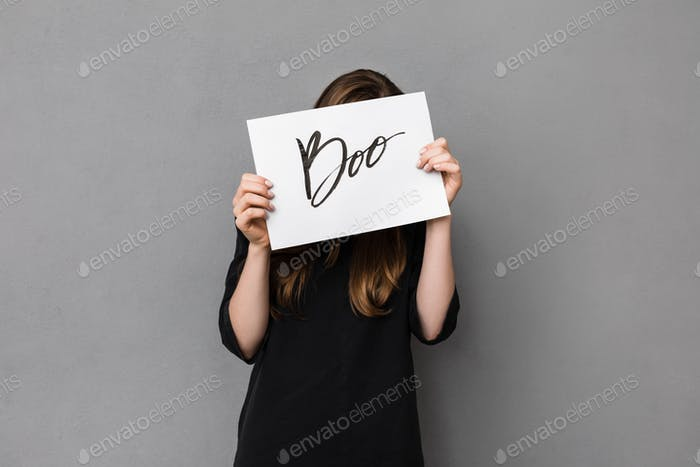 Portrait of pretty girl standing and covering her face while holding postcard on gray background