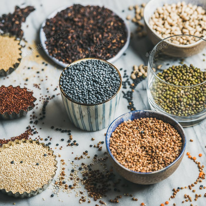 Various raw uncooked grains, beans, cereals in bowls and cups