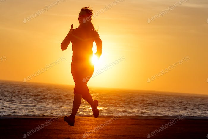 Woman running with ocean view at sunset