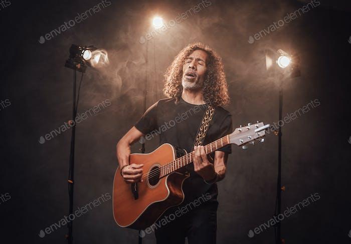 Talentierte spanische Musiker in schwarzem T-Shirt Gitarre spielen