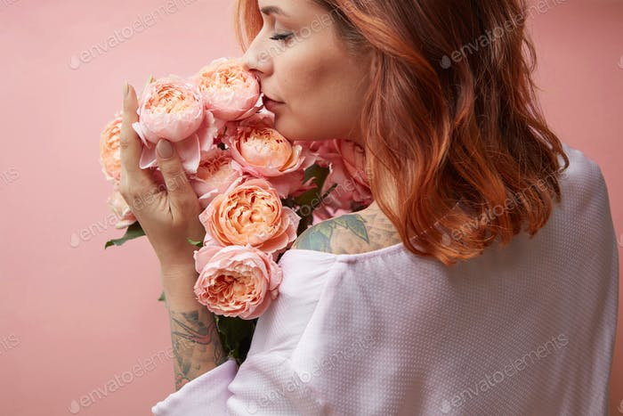 A girl with a tattoo holds a bouquet of flowers roses on a pastel background in a trendy color of