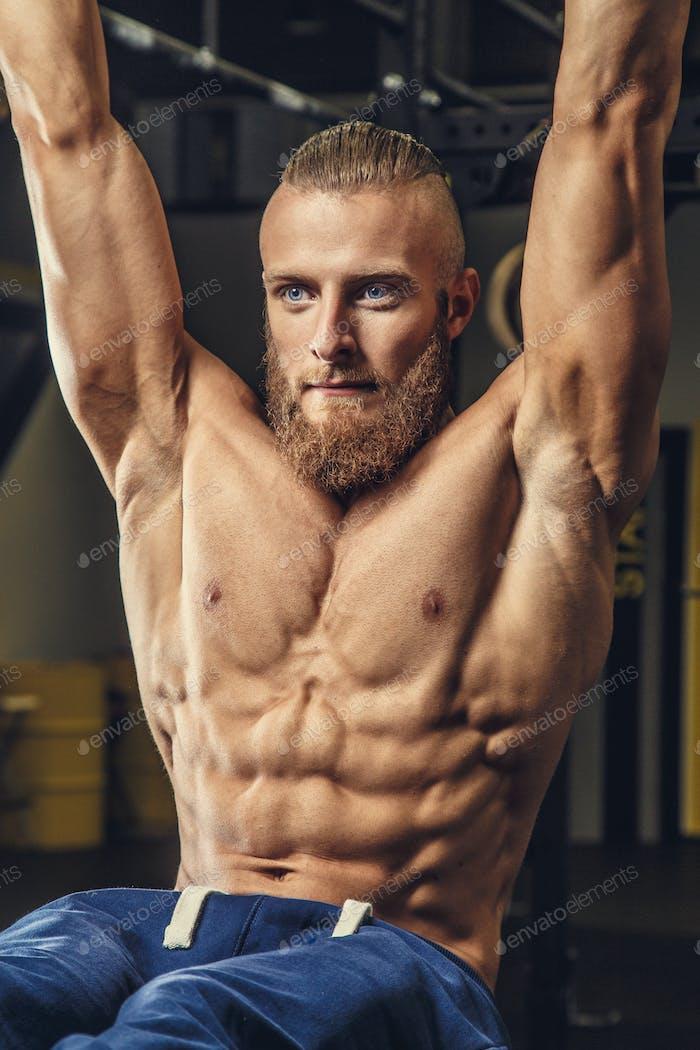 Shirtless muscular guy with beard.