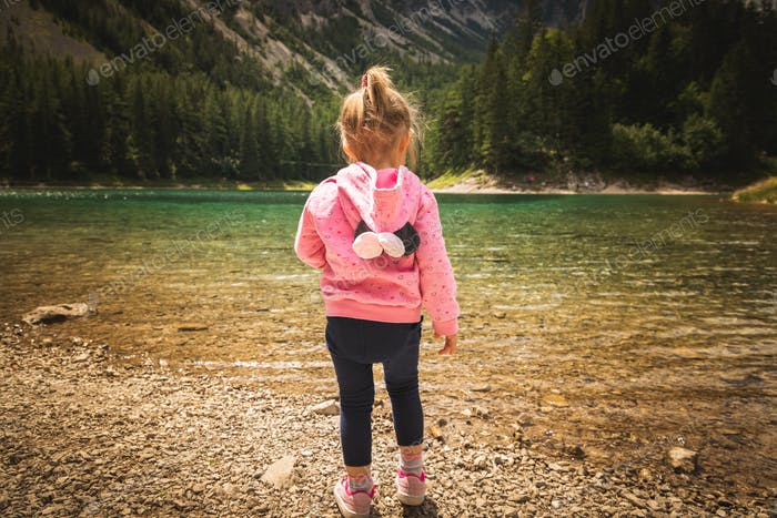 2-3 year old child with diper standing at Gruner see, Green lake rocky shore.