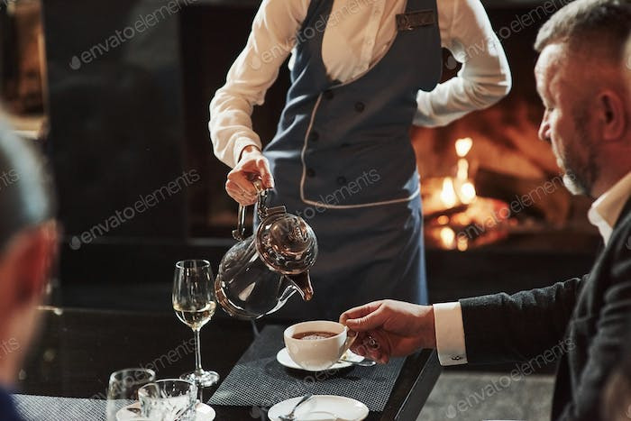 Friends sits in the restaurant with beautiful fireplace in it