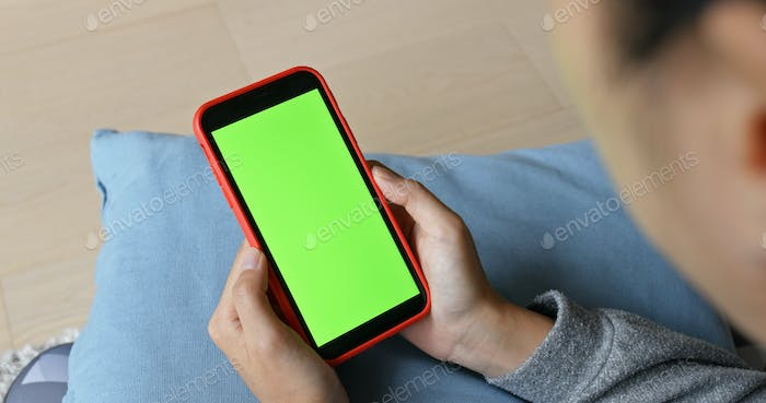 Woman use of mobile phone with green screen at home