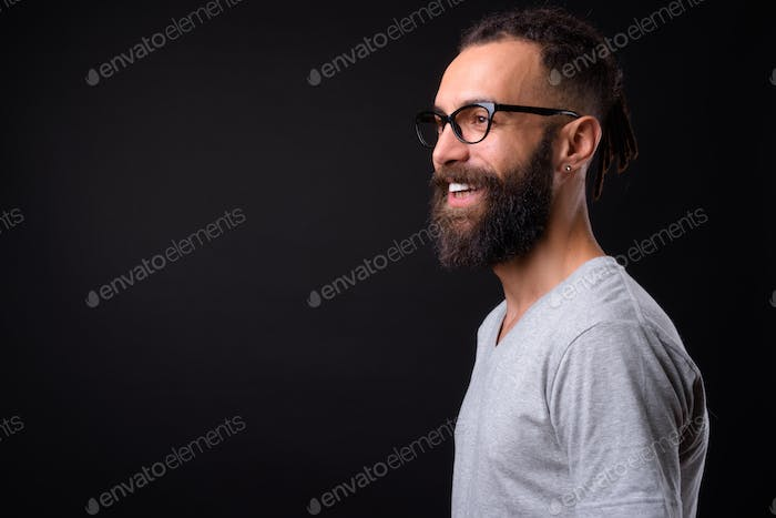 Young handsome Persian man with dreadlocks against black background