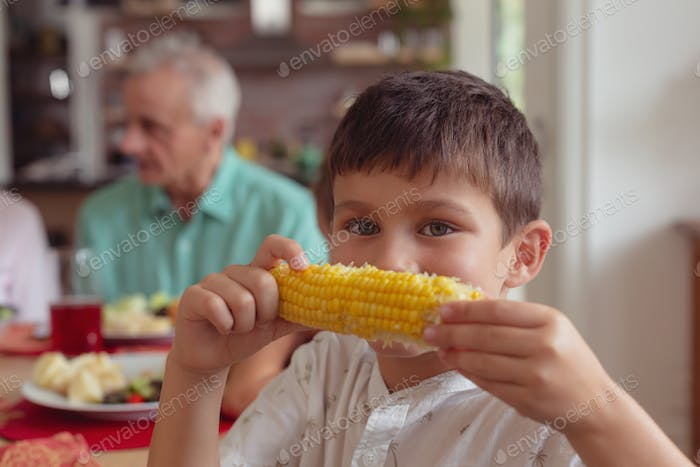 Portrait of Caucasian boy holding maize at dining table at home