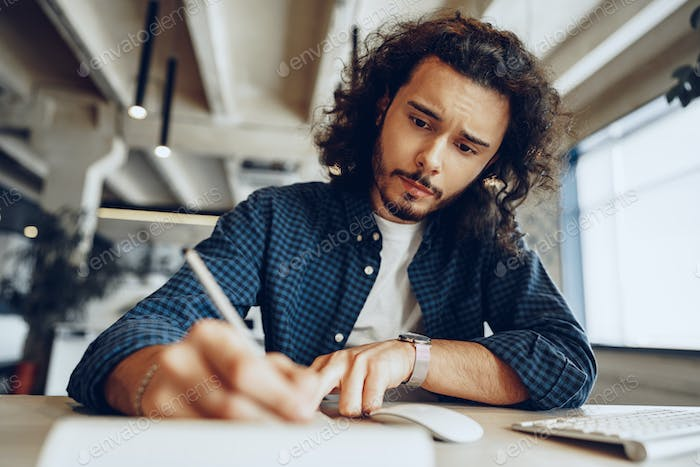 Handsome curly guy is making notes at the working table in open space office