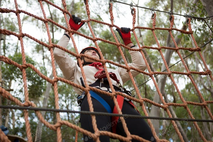 Woman wearing safety helmet climbing on a rope fence