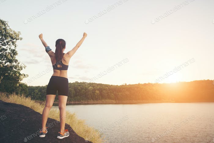 Young fitness woman achieve hiking on peak with lake view sunset.