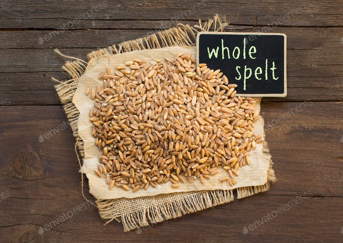 Whole unpolished spelt in a with a small chalkboard