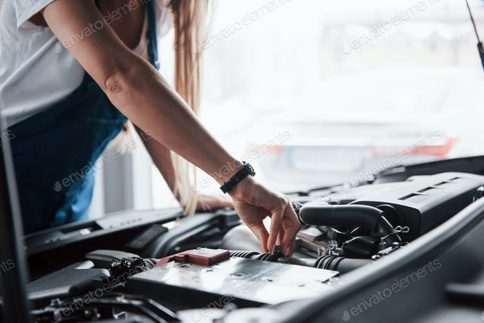 En el hermoso trabajo. Coche adicto mujer reparaciones coche negro interior