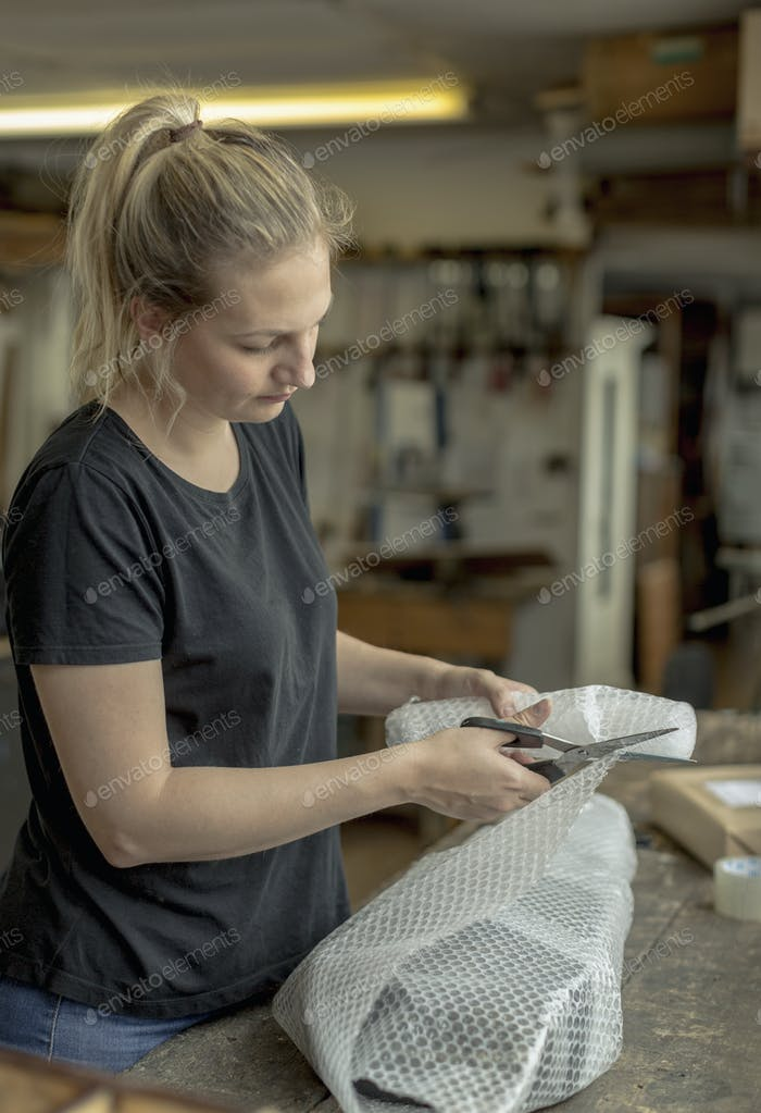 Blond woman standing in a workshop, cutting bubble wrap with pair of scissors, wrapping a parcel for