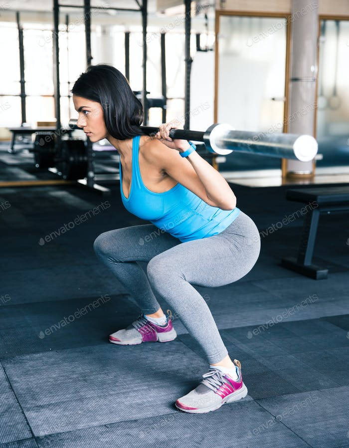 Young fit woman working out with barbell