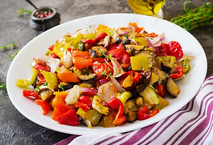 Baked vegetables on white plate. Eggplant, zucchini, tomatoes, paprika and onions