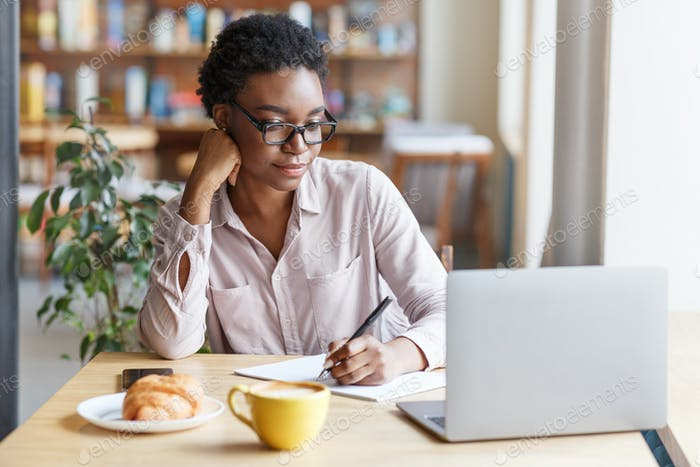 Online education. Serious black girl studying remotely on laptop from city cafe