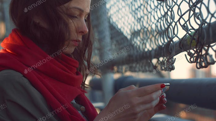Young girl with a phone on a bridge in NYC