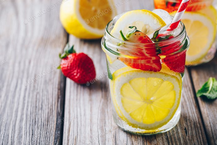 Lemon and strawberry lemonade in glass mason jars on a wooden background.