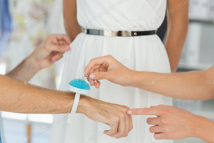 Closeup of two fashion designers adjusting dress on model in the studio
