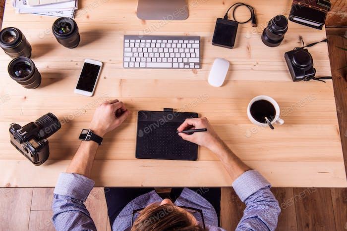 Fotograf am Schreibtisch, Bürogeräte und Objektiv