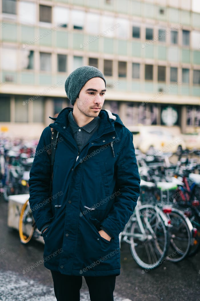 Young man in the city with bicycles in the background