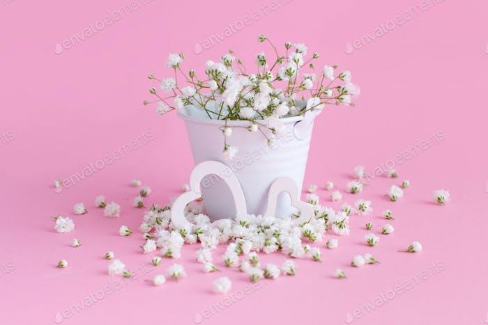 Kleine weiße Blumen und Herzen auf rosa Hintergrund