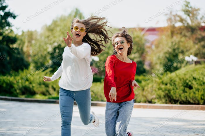 cheerful joyful portrait  of two best happy girls jumping and have fun in the sunny park