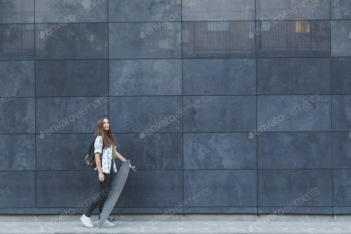 Beautiful young girl posing on her skateboard near the wall of modern building